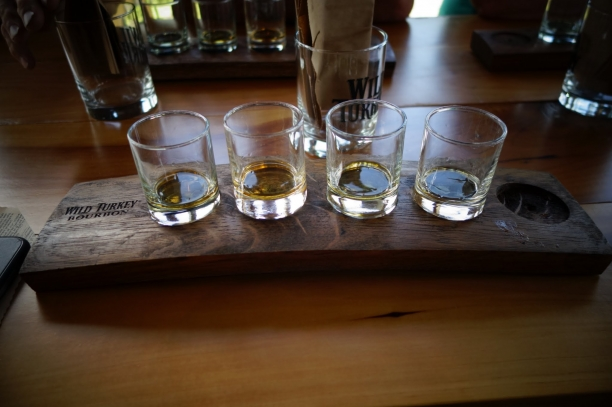 Why go on a Catholic pilgrimage? My reason was these four rocks glasses, with different shades of bourbon, lined up horizontally on top of a wooden bourbon flight board.