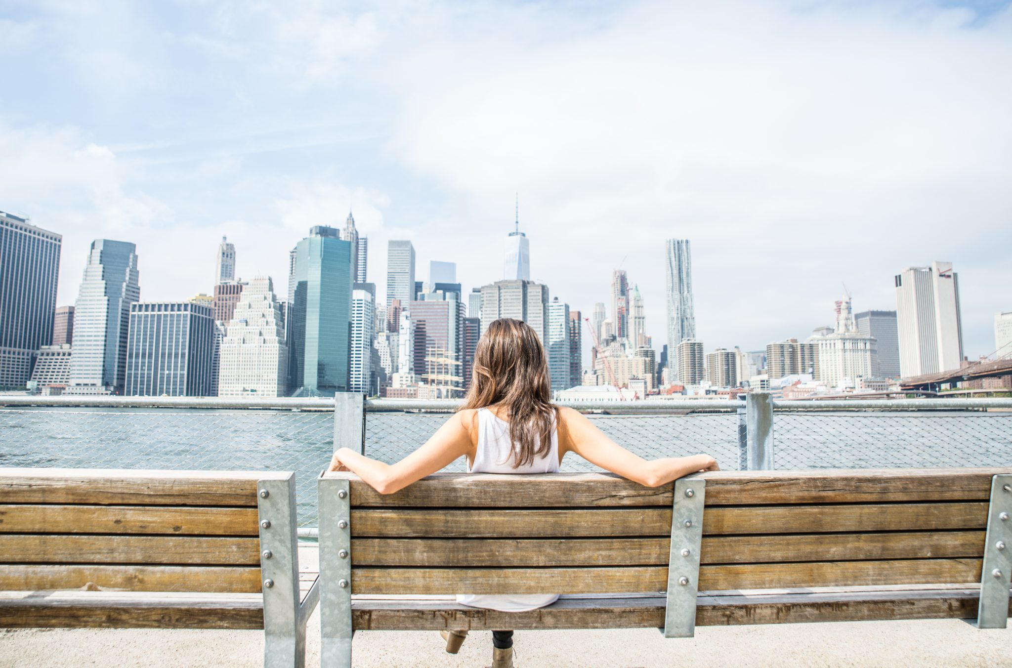 This woman knows how to enjoy being single, sitting confidently on a wooden bench with her back to the camera. She's looking out across a river at a busy city skyline.