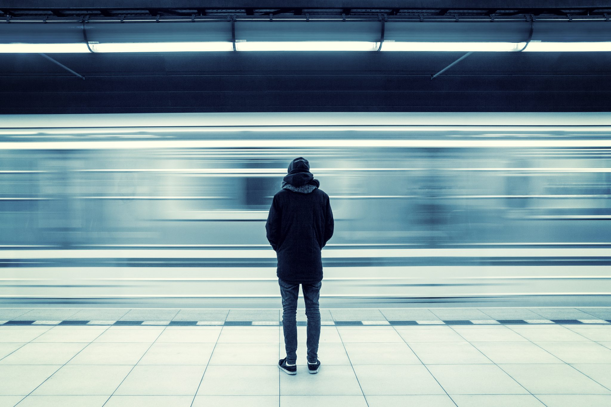 Man stuck in the typical American Dream, standing with his back to the camera in front of the blur of a subway whizzing by.