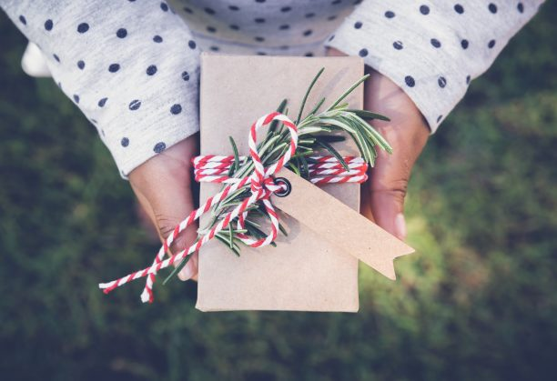 Ethical shopping gift-giving guide — a close-up of a young girl's hands holding a Christmas present.