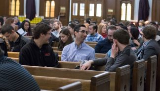 This is how to stop parish-hopping and find a parish to call your own, like these young adults sitting in pews in a church. Photo credit: Archdiocese of Washington.